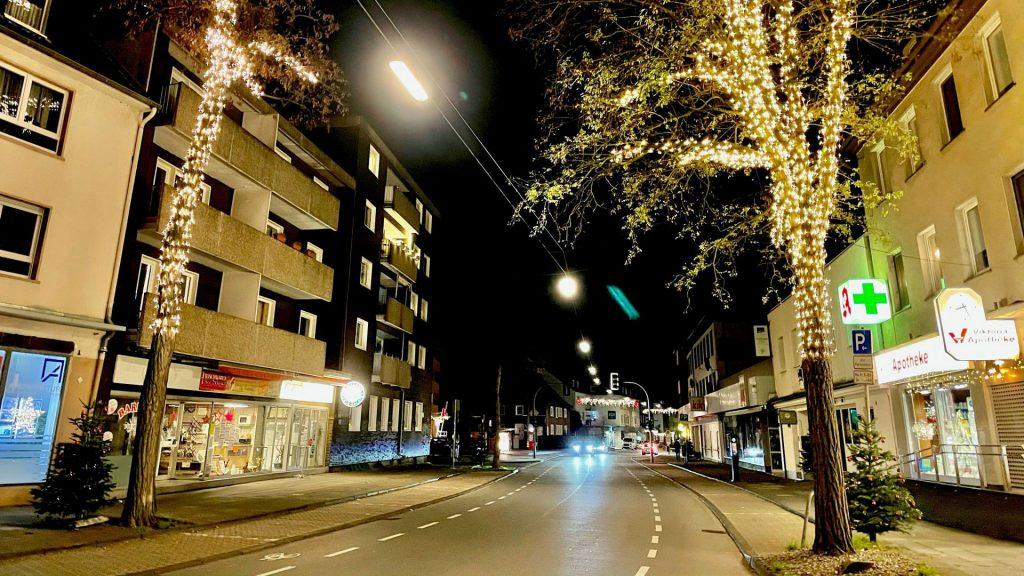 Straße mit zwei Bäume, die mit Lichterketten beschmückt sind.